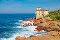 Cliffs of the Tuscan coast, overlooking the sea stands the castle of Boccale, medieval manor with watchtower in Livorno Royalty Free Stock Photo