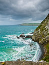 Cliffs under thunder clouds and turquoise ocean Royalty Free Stock Photos