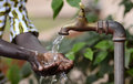 Climate Change Symbol: Handful Of Water Scarsity for Africa Symbol. Hand of an African black boy with water pouring from a tap. Royalty Free Stock Photo