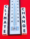 Climate change text inscribed in uppercase letters on small white cubes alongside a thermometer red background Royalty Free Stock Images