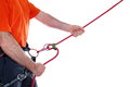 Climber belay with orange shirt and red rope Stock Images