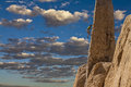 Climber struggles up a cliff rock clings to the edge of challenging in joshua tree national park Stock Image