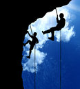 Climbers climbing a mountain on clouds sky background Stock Photo