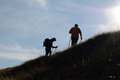Climbers silhouette of two men trekking on the mountain at sunset Royalty Free Stock Images