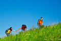 Climbing the hill friends with backpacks on summer Royalty Free Stock Photos