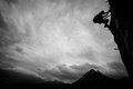 Climbing silhouette of a climber above mountain peaks Stock Images