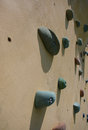 Climbing wall grungy surface of an artificial rock with toe and hand hold studs Stock Images