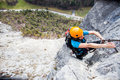 Climbing young woman scaling a rock face Royalty Free Stock Image