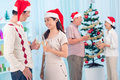 Clinking glasses festive couple in the foreground to celebrate christmas Royalty Free Stock Photo