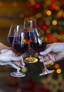 Clinking glasses of wine in hands on bright christmas lights bac Royalty Free Stock Photo