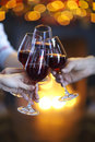 Clinking glasses of wine in hands on bright lights background Royalty Free Stock Photo