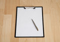 Clipboard with blank paper and a pen on the table Royalty Free Stock Photo