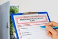 Clipboard with Emergency Evacuation Plan beside Exit Door Royalty Free Stock Photo