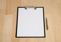 Clipboard and a pen on the table with blank paper Royalty Free Stock Photography