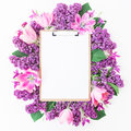 Clipboard, tulips and lilac branch on pink background. Flat lay, top view. Beauty blog concept. Royalty Free Stock Photo