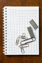 Clips and staples on the notebook on the wooden table Royalty Free Stock Image