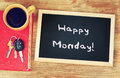 Clock, coffee cup and blackboard with the phrase happy monday!
