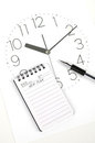 Clock face and notepad with pen Royalty Free Stock Images