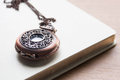 Clock locket with book in table Stock Photo