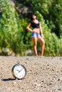Clock on the stone road and blurred girl at sunny day. Royalty Free Stock Photo
