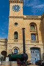 Clock tower of Malta Maritime Museum with old steam engine in front Royalty Free Stock Photo