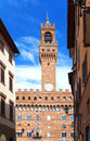 The clock tower of the Old Palace (Palazzo Vecchio) in Signoria Square, Florence (Italy) against the blue sky Royalty Free Stock Photo