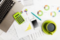 Close of business workplace with financial reports and office stuff still life Stock Images