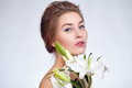 Close portrait of a beautiful young girl with lily flowers. Royalty Free Stock Photo