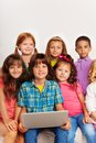 Close portrait of kids with laptop large group sitting on the coach and smiling Royalty Free Stock Photos