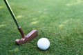 Close of putter and ball golf lying on the grass next to the stick Royalty Free Stock Images