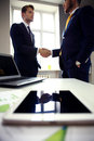 Close-shot of a tablet computer with businessmen handshaking Royalty Free Stock Photo