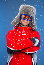 Close up of active man freezing in snow standing winter hat and coat isolated over blue background Stock Photos