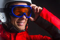 Close up of active smiling guy in ski hamlet and glass mask standing isolated over black background Royalty Free Stock Images