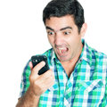 Close-up of an angry man yelling at his mobile phone Royalty Free Stock Photo