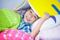 Close up asian boy covering head with book and smiling educati handsome notebook lying on bed in bedroom looking at camera Royalty Free Stock Image