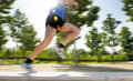 Close up athletic legs of young man running in city park on summer training in healthy lifestyle concept with trees the background Stock Image