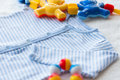 Close up of baby bodysuit for newborn and rattle Royalty Free Stock Photo