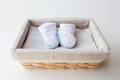 Close up of baby bootees for newborn boy in basket Royalty Free Stock Photo