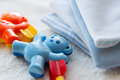 Close up of baby rattle and clothes for newborn Royalty Free Stock Photo