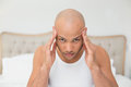 Close up of bald man suffering from headache in bed a young at home Royalty Free Stock Images