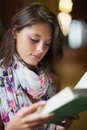 Close up of a beautiful female student reading a book against blurred background Stock Photography