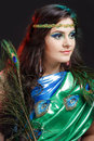 Close up beauty portrait of beautiful girl with peacock feather, headband. Creative makeup peafowl feathers. Attractive Royalty Free Stock Photo