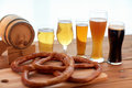 Close up of beer glasses, barrel and pretzels Royalty Free Stock Photo