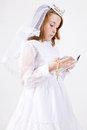 Close up below young girl smiling her first communion dress veil reading bible holding her rosary beads cross Stock Photography