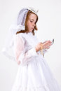 Close up below young girl smiling her first communion dress veil reading bible holding her rosary beads cross Royalty Free Stock Photo