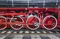 Close-up of black heritage steam train on railway tracks with red wheels and transmission engine Royalty Free Stock Photo