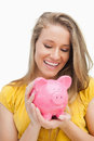 Close-up of a blond woman looking a piggy-bank Stock Photography