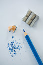 Close-up of blue color pencil with pencil shaving and sharpener Royalty Free Stock Photo