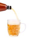 Close up of bottle of beer pouring into a mug white background Stock Photos