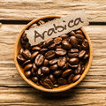 Close up of a bowl of arabica coffee beans full over an old wooden table Stock Images
